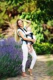 有吊索的走在公园的男婴的愉快的微笑的母亲 免版税库存图片