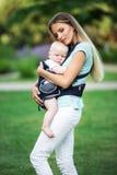 有吊索的走在公园的男婴的愉快的母亲 免版税库存图片