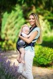 有吊索的走在绿色公园的男婴的愉快的微笑的母亲 免版税图库摄影