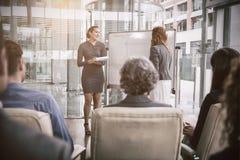 有同事的女实业家在会议期间 库存图片