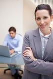 有同事的微笑的女实业家他的在她之后的膝上型计算机的 免版税库存图片