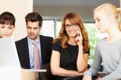 有同事的愉快的女实业家在背景中 免版税库存图片