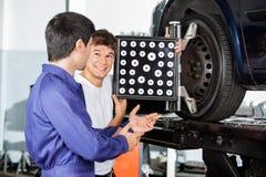 有同事的技工,当使用轮子直线对准器时 免版税库存图片