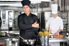 有同事的确信的厨师在厨房里 免版税库存图片