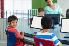 有同学的在计算机期间的男孩和老师分类 图库摄影