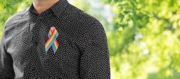 有同性恋自豪日彩虹了悟丝带的人 免版税库存图片