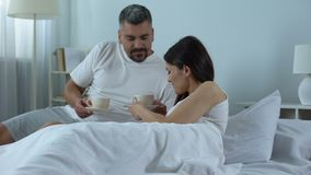 有同情心的丈夫在床上的带来芬芳新鲜的咖啡给心爱的妻子,蜜月 影视素材