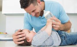 有同情心的对婴孩的父亲哺养的牛奶 库存图片