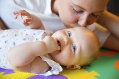 有同情心的母亲亲吻她微笑的和逗人喜爱的女婴 免版税库存图片
