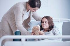 有同情心的母亲和病的女儿 免版税库存图片