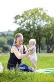 有同情心的母亲抱着婴孩,反对夏天公园 免版税库存图片