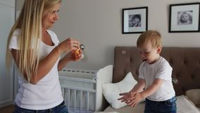 有同情心的母亲演奏看肥皂泡的儿子,男孩是愉快跳在床上 影视素材