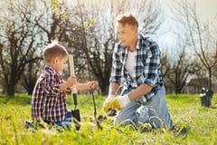 有同情心的种植树的父亲和小儿子 免版税图库摄影