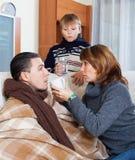 有同情心的妻子和爱恋的儿子围拢的病的人 图库摄影