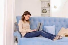 有同情心的妻子选择礼物在网上在家庭的膝上型计算机并且支付  图库摄影