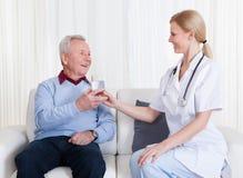 有同情心的医生Giving Water To Patient 免版税库存照片