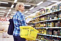 有名单购物的妇女主妇在百货商店植物油 库存图片