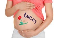 有名字的在她的肚子写的卢卡斯,特写镜头年轻人孕妇 免版税库存照片