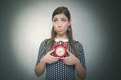 有后红色闹钟的有罪妇女工作或学校教训的 睡过头 迟到者 免版税库存照片