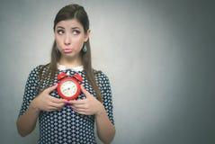 有后红色闹钟的有罪妇女工作或学校教训的 睡过头 迟到者 库存照片