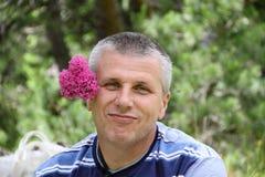 有后边一朵桃红色花的一个英俊的人 免版税库存照片