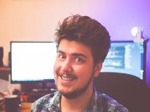 有后边两台显示器的疯狂的看起来的讨厌的微笑的人开发商自由职业者 库存照片