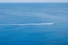 有后边长的足迹的唯一白色汽船 免版税图库摄影