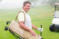 有后边高尔夫球儿童车的愉快的高尔夫球运动员 库存照片