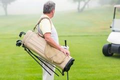 有后边高尔夫球儿童车的愉快的高尔夫球运动员 图库摄影