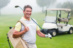有后边高尔夫球儿童车的愉快的高尔夫球运动员 库存图片