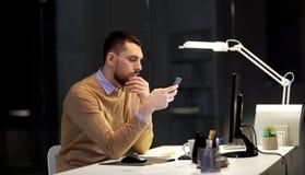 有后运转在夜办公室的智能手机的人 库存图片
