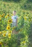 有向日葵篮子的一个微笑的男孩  微笑的男孩用向日葵 向日葵的领域的一个逗人喜爱的微笑的男孩 免版税库存图片
