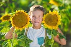 有向日葵篮子的一个微笑的男孩  微笑的男孩用向日葵 向日葵的领域的一个逗人喜爱的微笑的男孩 免版税图库摄影