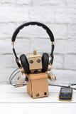 有听到从一个手机的音乐的耳机的机器人 库存图片