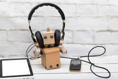 有听到从一个手机的音乐, ly的耳机的机器人 免版税库存照片