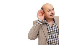 有听力丧失的老年人设法听声音 免版税库存照片