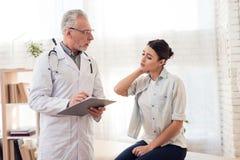 有听诊器和女性患者的医生在办公室 耐心` s脖子创伤 库存照片