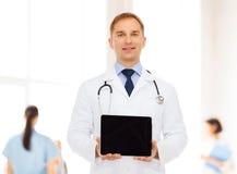 有听诊器和片剂个人计算机的微笑的男性医生 免版税库存图片