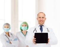 有听诊器和片剂个人计算机的微笑的男性医生 免版税库存照片