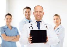 有听诊器和片剂个人计算机的微笑的男性医生 库存照片