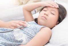 有听诊器的一点手医生检查病的女孩 免版税图库摄影