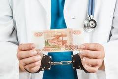 有听诊器的医生和5000副钞票和手铐 一个哥斯达黎加 库存图片