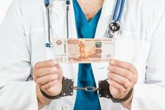有听诊器的医生和5000副钞票和手铐 一个哥斯达黎加 免版税库存照片