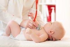 有听诊器的医生审查的婴孩在诊所 婴孩健康概念 免版税库存图片