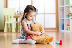 有听诊器的小孩女孩和玩具熊坐地板,在家庭内部背景 库存照片