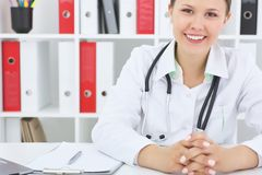 有听诊器的年轻美丽的医生在办公室背景中 免版税库存照片