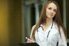 有听诊器的微笑的家庭医生 医疗保健 15个妇女年轻人 研究生 在一个医学机关 白色长袍 免版税库存照片