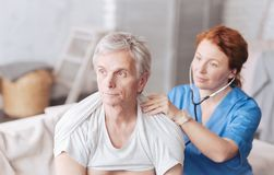 有听诊器的快乐的护士听患者的肺声音的 库存图片