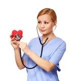 有听诊器的护士审查红色心脏的 库存照片
