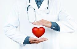 有听诊器的男性医生显示心脏形状 免版税图库摄影